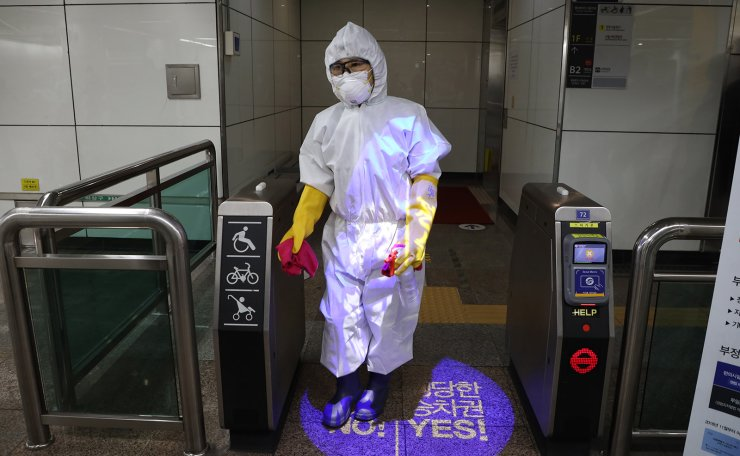 A worker wearing protective gears sprays disinfectant as a precaution against the new coronavirus at a subway station in Seoul, South Korea, Friday, Feb. 28, 2020. Korea Times photo by Choi Won-suk