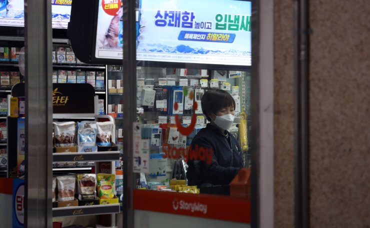 A store manager wears a face mask at a convenience store in Seoul, March 2, 2020. Korea Times photo by Choi Won-suk