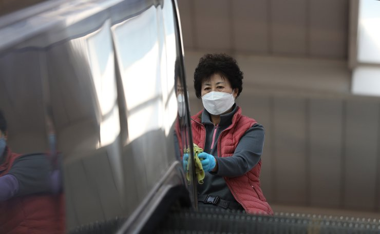 A worker wearing a face mask disinfects as a precaution against the new coronavirus at Seoul Railway Station in Seoul, South Korea, Wednesday, March 2, 2020. Korea Times photo by Choi Won-suk