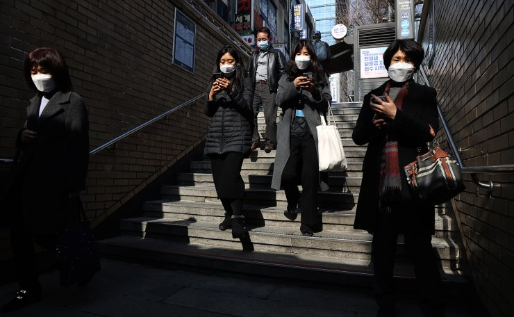 People wearing face masks walk at the Seoul Railway Station in Seoul, South Korea, Wednesday, March 4, 2020. Korea Times photo by Choi Won-suk