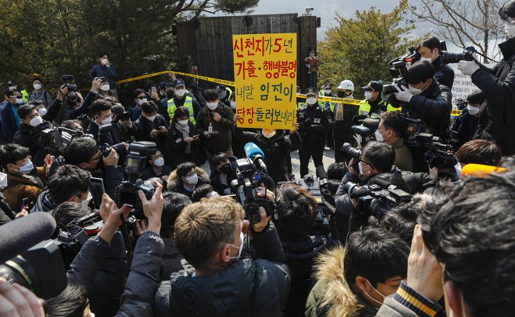 Protesters condemn Lee Man-hee ,a leader of Shincheonji Church of Jesus, as Lee holds a press conference in Gapyeong, South Korea, Monday, March 2, 2020. In the hastily arranged news conference Lee, the 88-year-old leader of a religious sect which has the country's largest cluster of infections, bowed down on the ground twice and apologized for causing the