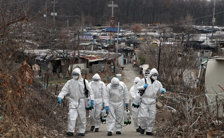 South Korean soldiers wearing protective gears walk to spray disinfectant as a precaution against the new coronavirus in Seoul, South Korea, Tuesday, March 3, 2020. Korea Times photo by Choi Won-suk