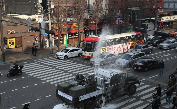 South Korean army trucks spray disinfectant as a precaution against the new coronavirus on a road in Seoul, South Korea, Wednesday, March 4, 2020. Korea Times photo by Choi Won-suk