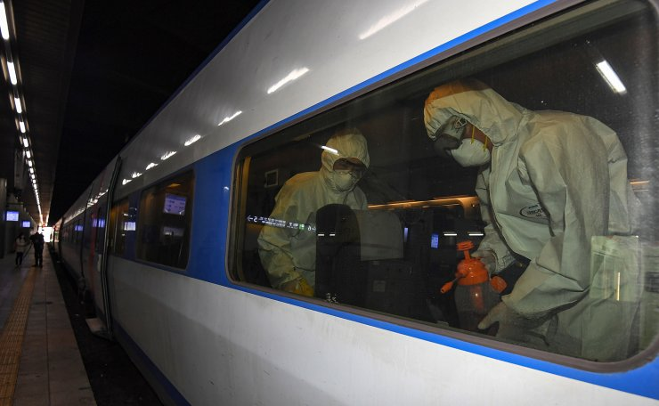 A disinfection worker, in protective gear, disinfects a passenger car of the KTX, at Seoul Railway Station in Seoul, South Korea, Wednesday, March 4, 2020. Korea Times photo by Shim Hyun-chul
