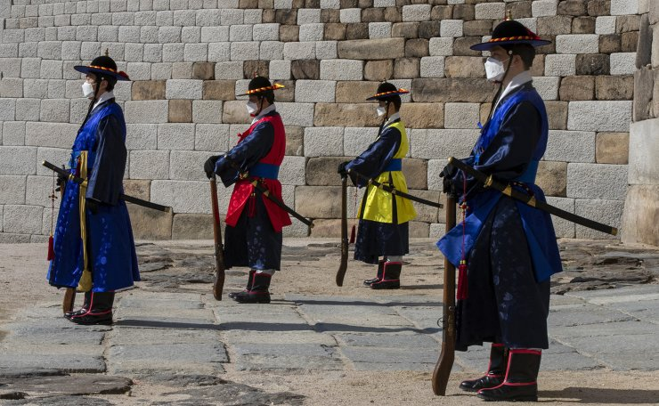 Imperial guards wearing face masks stand guard in front of the Sungnyemun Gate, Korea's National Treasure No. 1 in Seoul, South Korea, March. 04, 2020. Korea Times photo by Shim Hyun-chul
