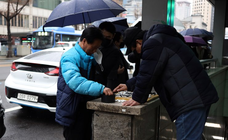 Two men play Go as they wait in a queue to buy face mask in Seoul, Tuesday, March 10, 2020. Korea Times photo by Choi Won-suk