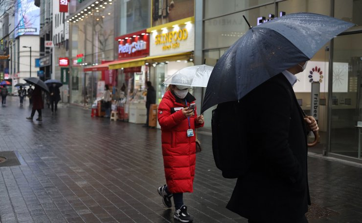 People wear face masks on a rainy day in Seoul, Tuesday, March 10, 2020. Korea Times photo by Choi Won-suk