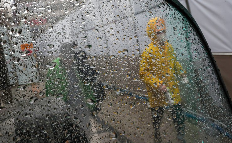 A man wearing a face mask is seen through the window on a rainy day in Seoul, Tuesday, March 10, 2020. Korea Times photo by Shim Hyun-chul