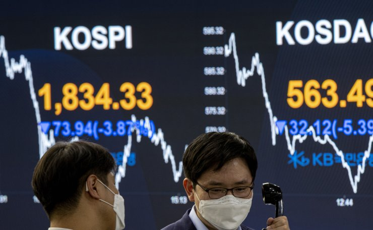 Currency traders wearing face masks watche monitors at the foreign exchange dealing room of the Kookmin Bank headquarters in Seoul, South Korea, Thursday, March 12, 2020. Korea Times photo by Shim Hyun-chul