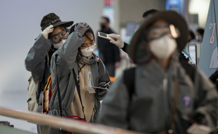 Passengers remove protective gears against Covid 19 for health examination processes before departure at Incheon International Airport in Incheon, South Korea, Friday, March 13, 2020. Korea Times photo by Shim Hyun-chul