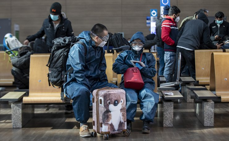 Passengers are seen wearing protective gears against Covid 19 as they wait for departure at Incheon International Airport in Incheon, South Korea, Friday, March 13, 2020. Korea Times photo by Shim Hyun-chul