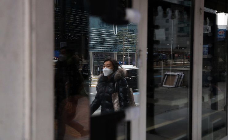 A woman is seen wearing a face mask at the Myeongdong shopping district in Seoul, Wednesday, March. 18, 2020. Korea Times photo by Choi Won-suk