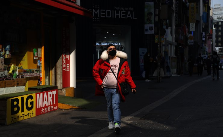A man is seen wearing a face mask at the Myeongdong shopping district in Seoul, Wednesday, March. 18, 2020. Korea Times photo by Choi Won-suk