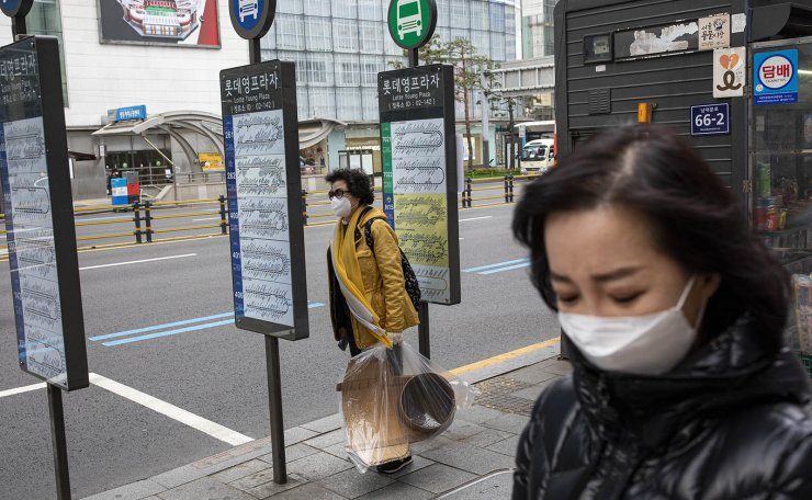 People are seen wearing face masks at the Myeongdong shopping district in Seoul, Wednesday, March. 18, 2020. Korea Times photo by Shim Hyun-chul