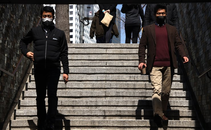 People are seen wearing face masks at the Myeongdong shopping district in Seoul, Thursday, March. 19, 2020. Korea Times photo by Choi Won-suk