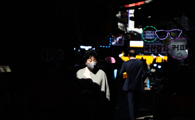 A woman is seen wearing a face mask at the Myeongdong shopping district in Seoul, Tuesday, March. 17, 2020. Korea Times photo by Choi Won-suk