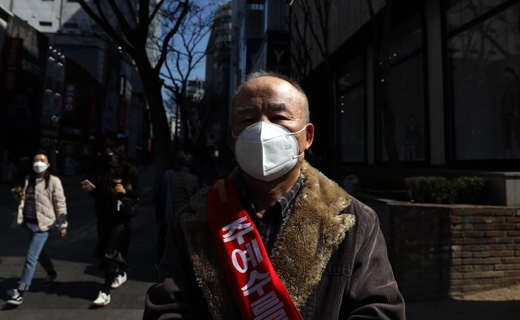 A man with a face mask preaches at the Myeongdong shopping district in Seoul, Monday, March. 16, 2020. Korea Times photo by Choi Won-suk