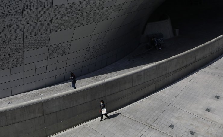 People are seen wearing a face mask at Dongdaemun Design Plaza in Seoul, South Korea, Thursday, March 19, 2020. Korea Times photo by Shium Hyun-chul