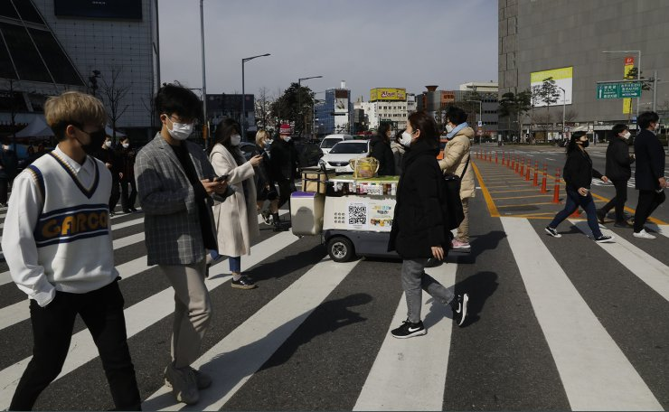People with face masks walk on a crosswalk near Dongdaemun Design Plaza in Seoul, South Korea, Thursday, March 20, 2020. Korea Times photo by Shim Hyun-chul