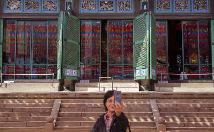 A Buddhist believer takes a selfie at the Jogyesa Buddhist temple in Seoul, South Korea. Korea Times photo by Shim Hyun-chul