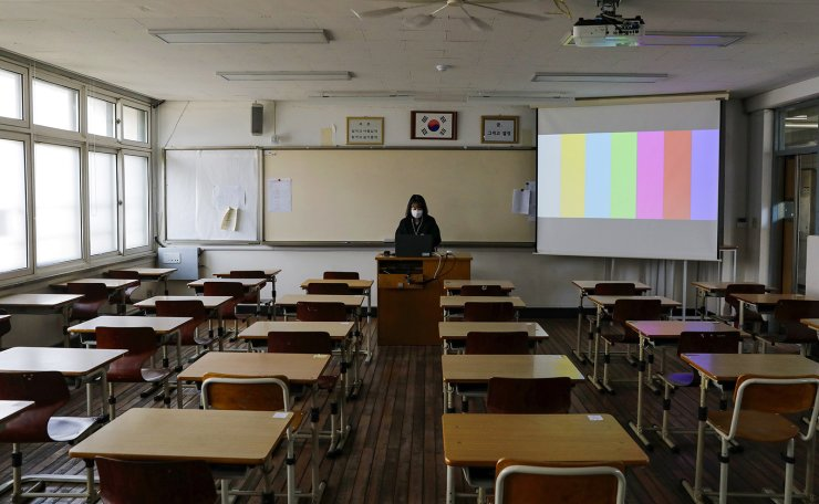 A teacher gives a class online from an empty classroom of Seoul Girls' High School in Seoul, Thursday, as the country finally started the new school year for seniors in middle and high schools after delays due to the COVID-19 outbreak. Korea Times photo by Shim Hyun-chul