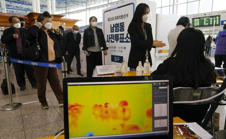 Voters wearing face masks wait in a line to cast their ballots while maintaining social distancing to help prevent the spread of the new coronavirus during an early voting for the April 15 general elections at a local polling station in Seoul, South Korea, Friday, April 10, 2020. Korea Times photo by Shim Hyun-chul