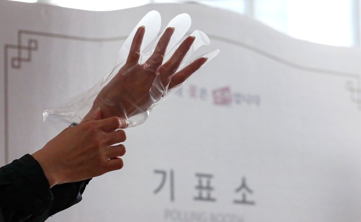 A voter wears a plastic glove to help protect against the spread of the new coronavirus during an early voting for the April 15 general elections at a local polling station in Seoul, South Korea, Friday, April 10, 2020. Korea Times photo by Shim Hyun-chul