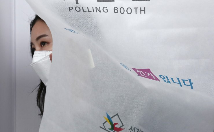 A voter wearing face mask to help protect against the spread of the new coronavirus casts early vote for the upcoming parliamentary election at a polling station in Seoul, South Korea, Friday, April 10, 2020. Korea Times photo by Shim Hyun-chul