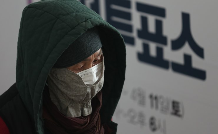 A voter wearing a face mask waits in a line to cast their ballots while maintaining social distancing to help prevent the spread of the new coronavirus during an early voting for the April 15 general elections at a local polling station in Seoul, South Korea, Friday, April 10, 2020. Korea Times photo by Shim Hyun-chul