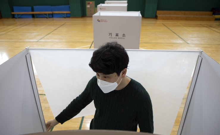 A staff memeber of National Election Commission prepares the polling booth ahead of the voting for the general elections at a local polling station in Seoul, South Korea, Tuesday, April 14, 2020. Korea Times photo by Choi Won-suk