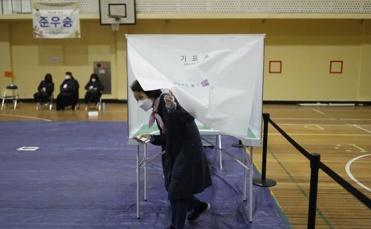A voter wearing a face mask to help protect against the spread of the new coronavirus exits out to cast his vote for the parliamentary elections at a polling station in Seoul, South Korea, Wednesday, April 15, 2020. Korea Times photo by Shim Hyun-chul