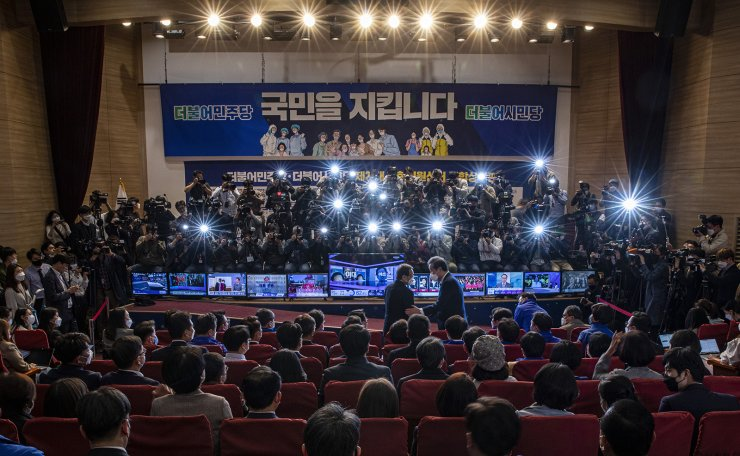 The ruling Democratic Party's members, lawmakers and supporters watch TVs broadcasting results of exit polls for the parliamentary election at the National Assembly in Seoul, South Korea, Wednesday, April 15, 2020. Korea Times photo by Shim Hyun-chul