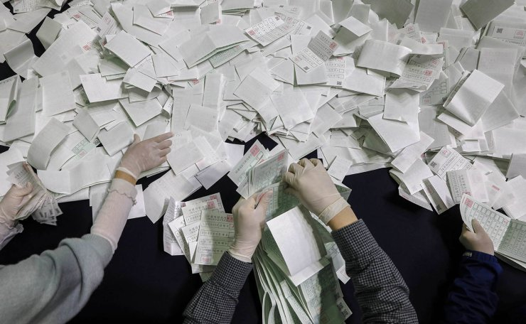 South Korean National Election Commission officials sort out ballots for counting at the parliamentary election at a ballot counting office in Seoul, South Korea, Wednesday, April 15, 2020. Korea Times photo by Shim Hyun-chul