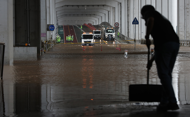 A worker begins the clean-up in the aftermath of a torrential rain storm that hit the capital city at Han River park on August 04, 2020 in Seoul, South Korea. Damage from heavy rain that pounded the country's central region earlier this week continued to grow, leaving 14 dead and 12 missing as of Tuesday. Korea Times photo by Shim Hyun-chul