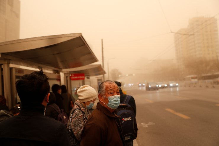 People wait for transportation at a bus stop as the city is hit by a sandstorm, in Beijing, China, March 15, 2021. In March, heavy sandstorms hit Beijing for the first time in six years, putting the country's reforestation efforts under scrutiny, with land increasingly scarce and trees no longer able to offset the impact of climate change. REUTERS