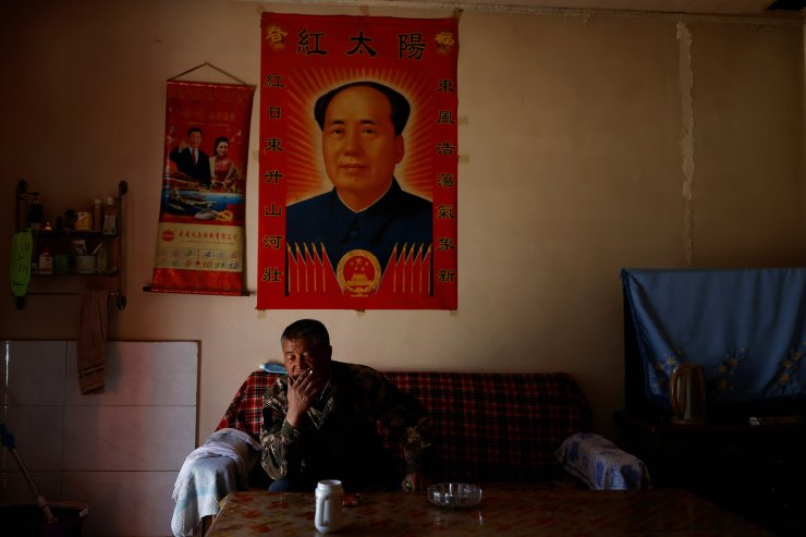 Wang Yinji, 53, sits in front of posters of late Chinese chairman Mao Zedong and Chinese President Xi Jinping and his wife Peng Liyuan, while smoking at his house in a village near the edge of the Gobi desert on the outskirts of Wuwei, Gansu province, China, April 14, 2021. 'After 1999, when the tree-planting sped up, things got much better,' said Yinji. 'Our corn grew taller. The sand that used to blow in from the east and northeast was stopped.' REUTERS