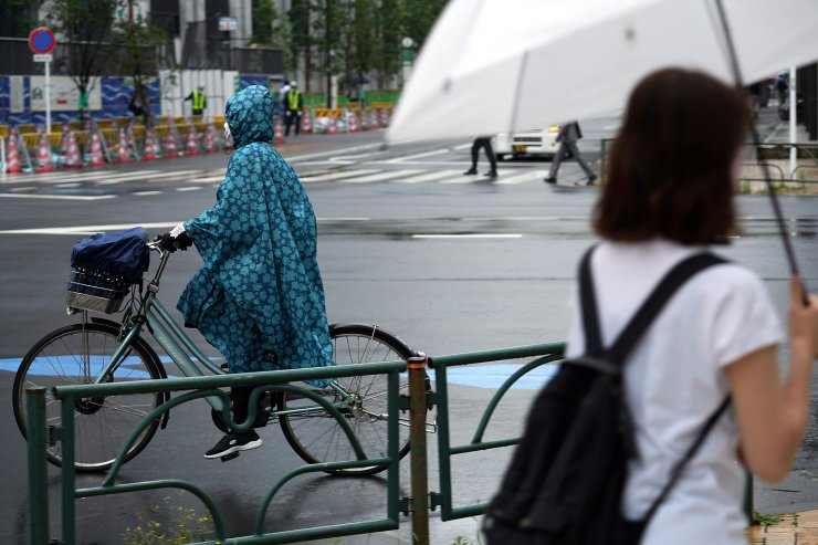 A woman wearing a protective mask to help curb the spread of the coronavirus rides a bicycle in the rain Monday, June 14, 2021, in Tokyo. Japan is desperately pushing to accelerate the pace of inoculations before the Tokyo Olympics. AP