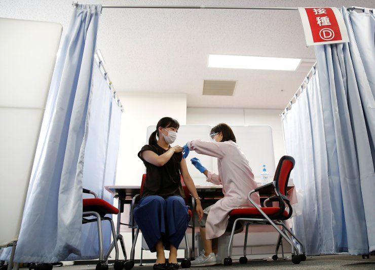 A cabin attendant of Japan Airlines (JAL) receives a dose of the Moderna coronavirus disease (COVID-19) vaccine at the company's facility at Haneda airport in Tokyo, Japan June 14, 2021. REUTERS
