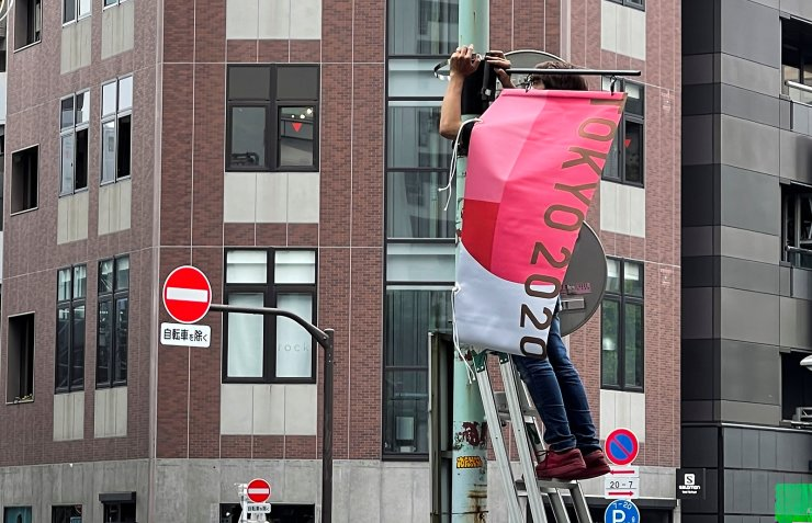 A worker attaches a Tokyo 2020 Olympic Games banner on a lamp post in Tokyo, Japan, June 16, 2021. REUTERS