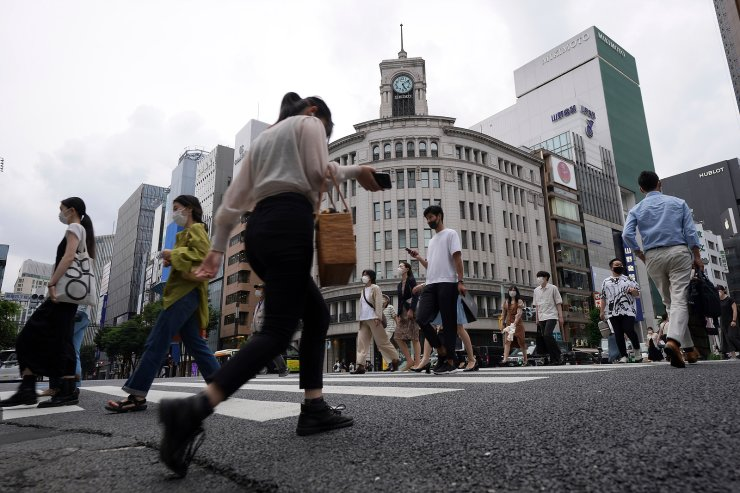 People wearing protective masks to help curb the spread of the coronavirus walk along a pedestrian crossing Wednesday, June 16, 2021, in Tokyo. The Japanese capital confirmed more than 500 new coronavirus cases on Wednesday. AP