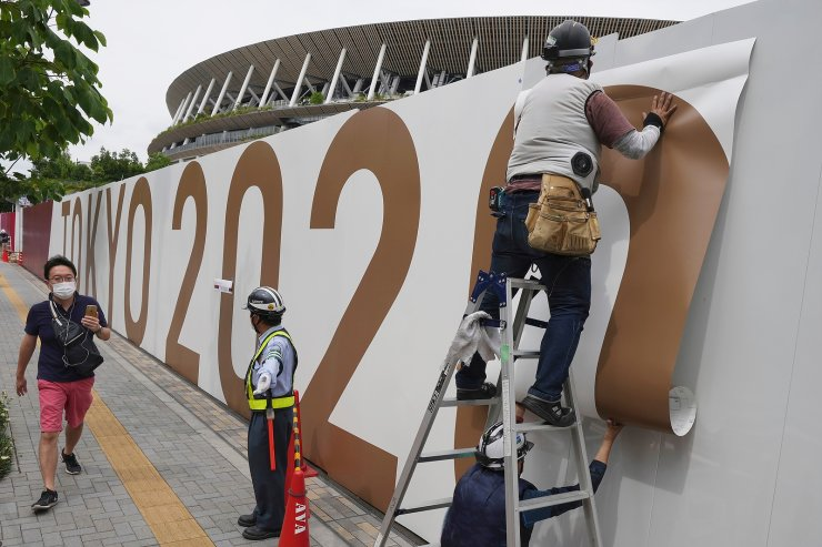 Workers paste the overlay on the wall of the National Stadium, where opening ceremony and many other events are scheduled for the postponed Tokyo 2020 Olympics, Wednesday, June 2, 2021, in Tokyo. AP