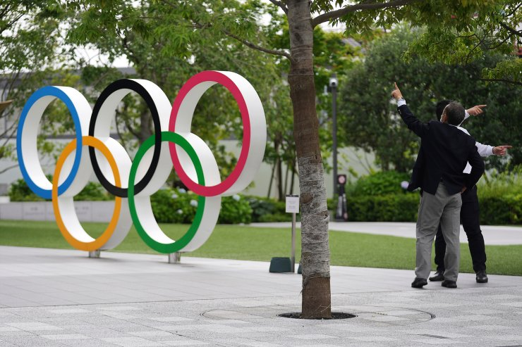 In this June 2, 2021, file photo,  men gesture near the Olympic Rings, in Tokyo. Public sentiment in Japan has been generally opposed to holding the Tokyo Olympics and Paralympics. This is partly based of fears the coronavirus will spike as almost 100,000 people — athletes and others — enter for both events. AP