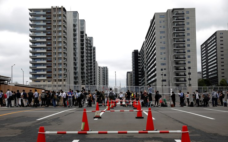 Journalists stand in a line to enter the village plaza of the Tokyo 2020 Olympic and Paralympic Village for a press tour in Tokyo, Japan, June 20, 2021.  REUTERS