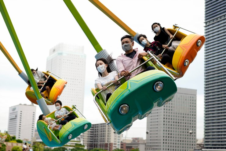 People wearing face masks enjoy an attraction ride at an amusement park in Yokohama, near Tokyo, Sunday, June 20, 2021. On June 17, Japan announced the easing of a coronavirus state of emergency in Tokyo and six other areas from next week, with new daily cases falling just as the country begins final preparations for the Olympics starting in just over a month. AP