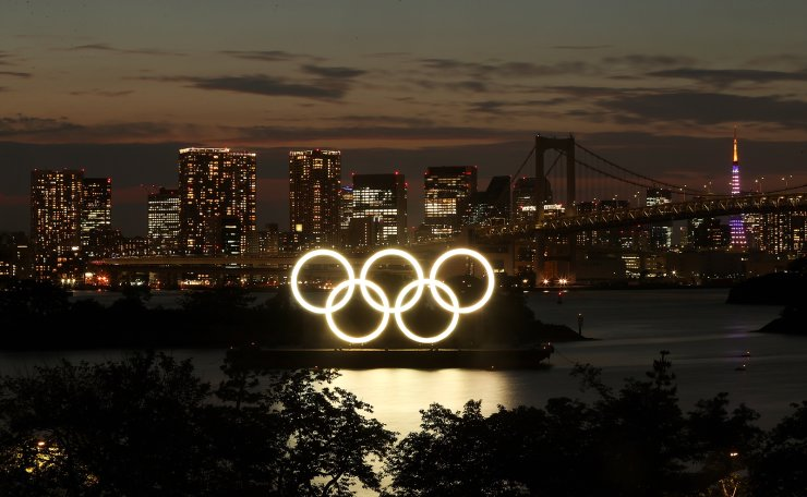 A general view of the Olympic Rings installed on a floating platform with the Rainbow Bridge in the background in preparation for the Tokyo 2020 Olympic Games in Tokyo, Japan June 21, 2021. Picture taken with long exposure. REUTERS