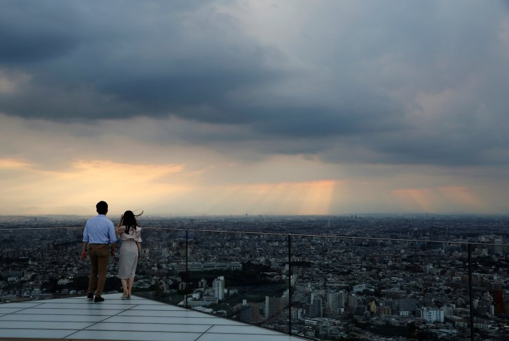 Visitors look at the skyline as they stand on Shibuya Sky, the observation deck of Shibuya Scramble Square, in Tokyo, Japan, June 1, 2021. REUTERS