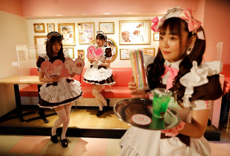 Cast members Hitomi, Kashima and Chia-can, greet guests at 'At-home Cafe', a maid cafe which is a subset of cosplay restaurants, in the Akihabara district, in Tokyo, Japan, June 8, 2021. REUTERS
