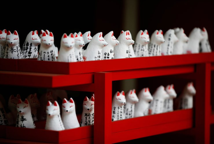 Miniature fox figures bearing worshiper's wishes are placed next to a shrine building at the Hie-Jinja Shinto Shrine in Tokyo, Japan, June 1, 2021. REUTERS