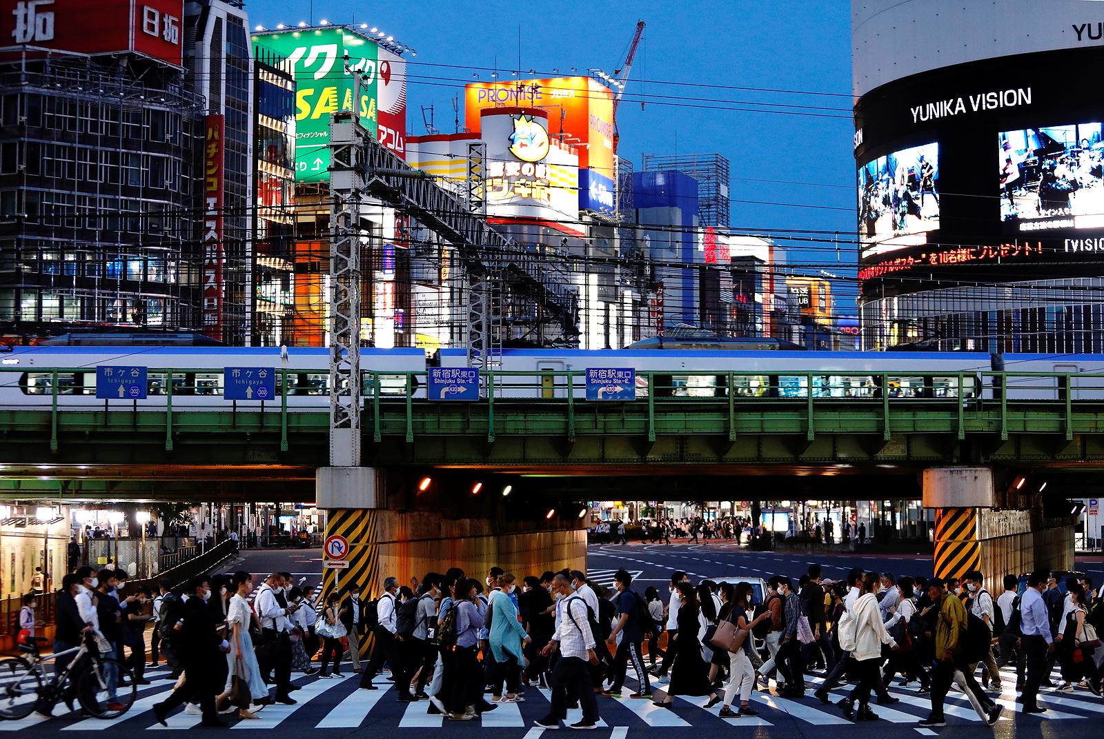 People cross a road in Shinjuku, Tokyo, Japan, June 3, 2021. REUTERS