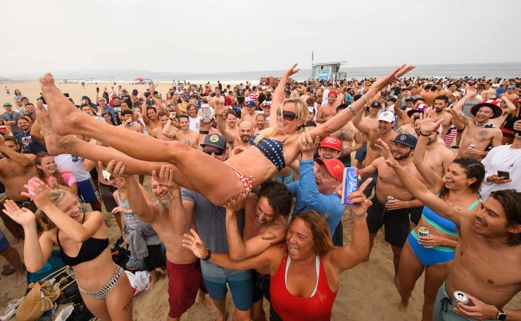 Repeat female champion Annie Seawright-Newton is lifted into the air after winning the 47th annual Hermosa Beach Ironman competition where participants must run a mile, paddle a surfboard a mile, and chug a six-pack of beer on July 4, 2021 in Hermosa Beach, California. AFP